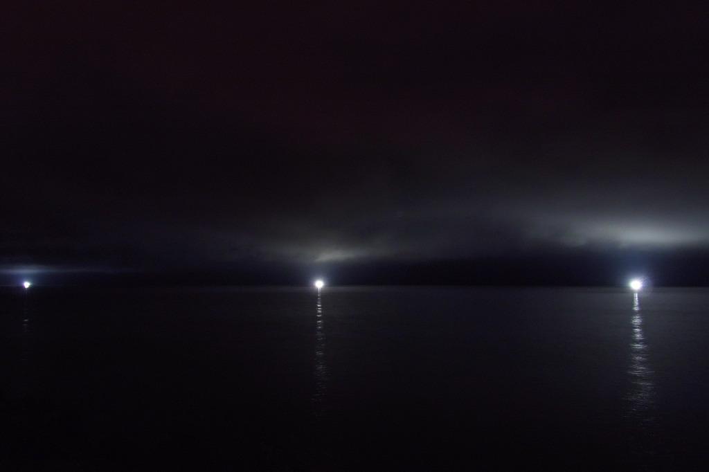 雲と海に照る漁火