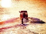 黄昏の水上ウェイクボードの練習