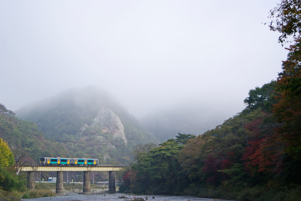 秋の久慈川を行く水郡線と朝もやに包まれた大だるま岩