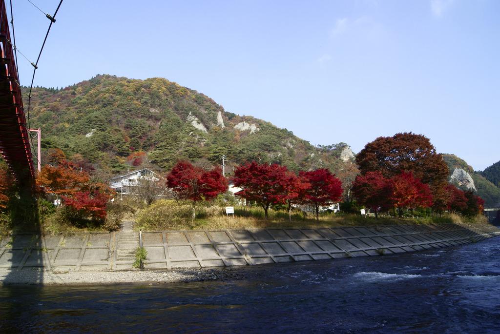 見上げるあゆのつり橋と錦秋の矢祭山の奇岩群