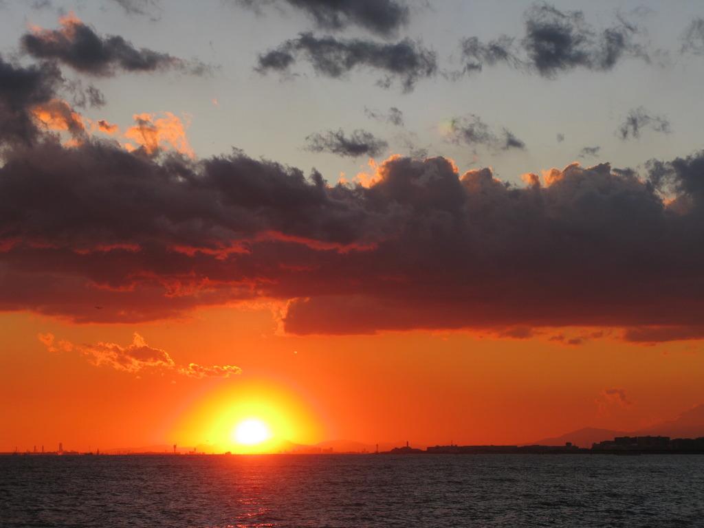 雲と海の間に太陽沈む