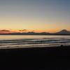 波と沈む夕陽と富士山