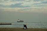 浜辺の親子とタンカー船